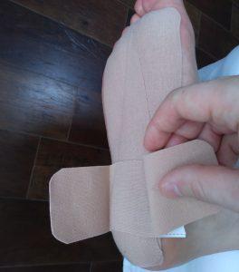 踵の痛むポイントにテープを貼る